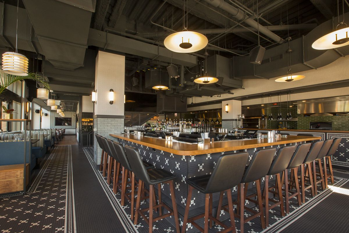 The modern-looking space features hanging lights, booth seating, and an open kitchen with hearths.