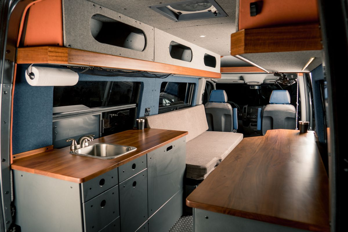 The inside of a camper van. There is a kitchenette with a sink, a seat, and a wooden table.