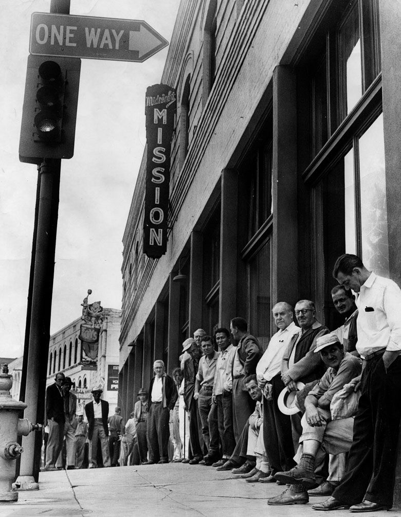 Men wait on the street at the door of theMidnightMissionat 326 South Los Angeles Street. Lodging and food are given to those who come to theMissionfor help. Photo dated: August 31, 1964.