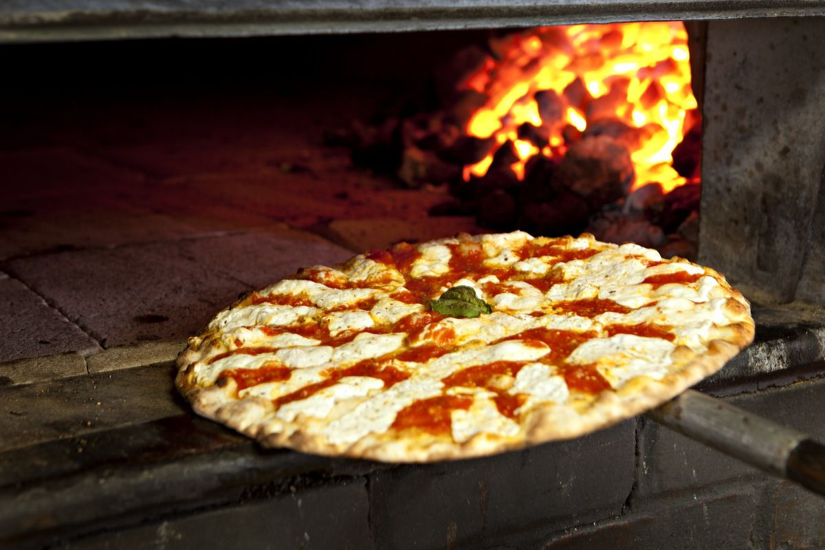 A tilted pizza in a warm oven with coal glowing at the back of the oven.