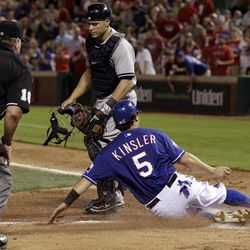 Texas Rangers' Ian Kinsler, bottom, scores on a Adrian Beltre single as home plate umpire Brian Runge, left, and New York Yankees catcher Russell Martin  look on in the sixth inning of a baseball game on Wednesday, April 25, 2012, in Arlington, Texas.