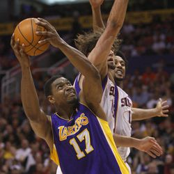 Los Angeles Lakers' Andrew Bynum (17) slips past Phoneix Suns' Robin Lopez, center, and Channing Frye during the first half of an NBA basketball game, Saturday, April 7, 2012, in Phoenix.