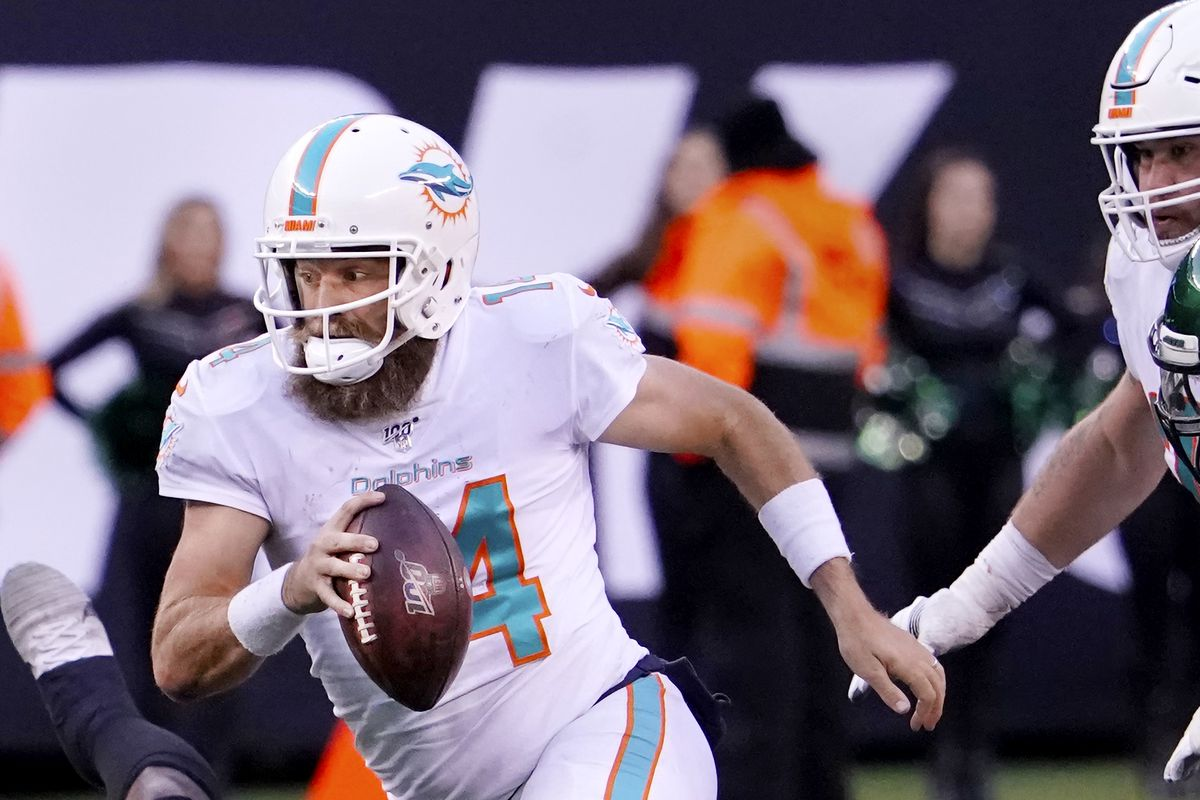 Ryan Fitzpatrick #14 of the Miami Dolphins runs out of the pocket with the ball in an NFL football game against the New York Jets on December 8, 2019 at MetLife Stadium in East Rutherford, New Jersey.