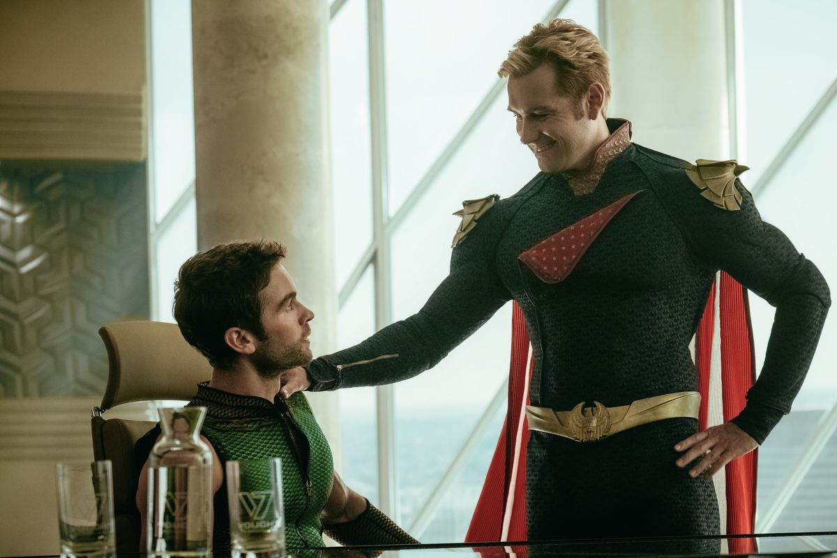 Homelander puts a hand on The Deep's shoulder during a pep talk at the Seven's home base in the live-action version of The Boys.