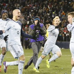 Sporting KC players swarm keeper Jimmy Nielsen as Sporting KC defeats Real Salt Lake Saturday, Dec. 7, 2013 in MLS Cup action.