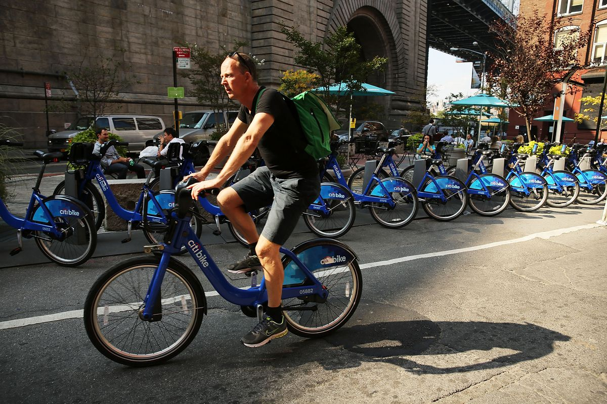 Photo of a man riding a ride share bike through Dumbo