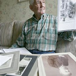 Mark Redford Brown looks at photos and memorabilia from his grandfather, who headed work on the Old Rock Church.