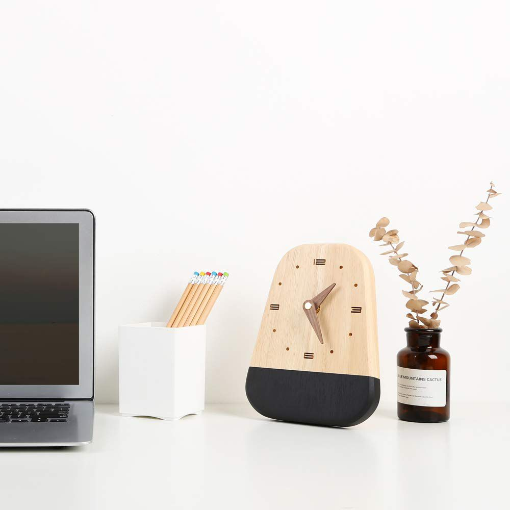 Desktop scene features a laptop, pencil holder, wood clock with black base, and a jar with dried flowers.
