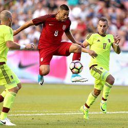 United States midfielder Clint Dempsey (8) kicks the ball between Venezuela defender Jose Manuel Velazquez (6) and Venezuela's Pablo Camacho (17) during a soccer game at Rio Tinto Stadium in Sandy on Saturday, June 3, 2017.
