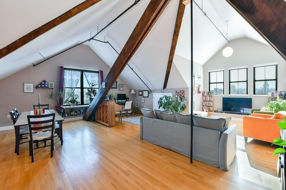 A living room-dining room-kitchen area beneath a dramatically soaring ceiling.