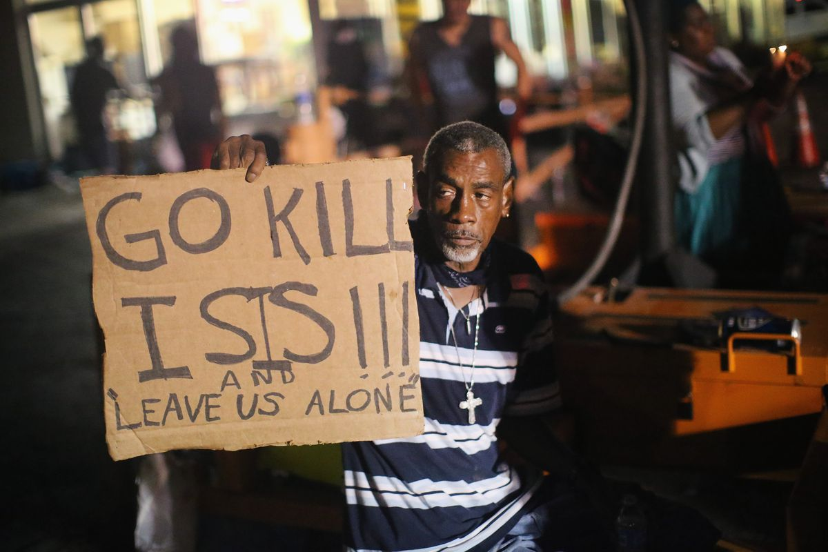 A man holds up a sign while protesting the shooting of Michael Brown in Ferguson, Missouri.