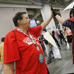 Salt Lake Comic Con security volunteer Robert Allen high-fives an attendee during the convention at the Salt Palace in Salt Lake City Friday, Sept. 5, 2014.