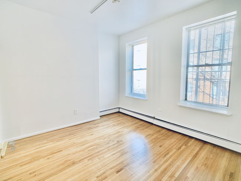 A living room with hardwood floors, white walls, and two large windows.