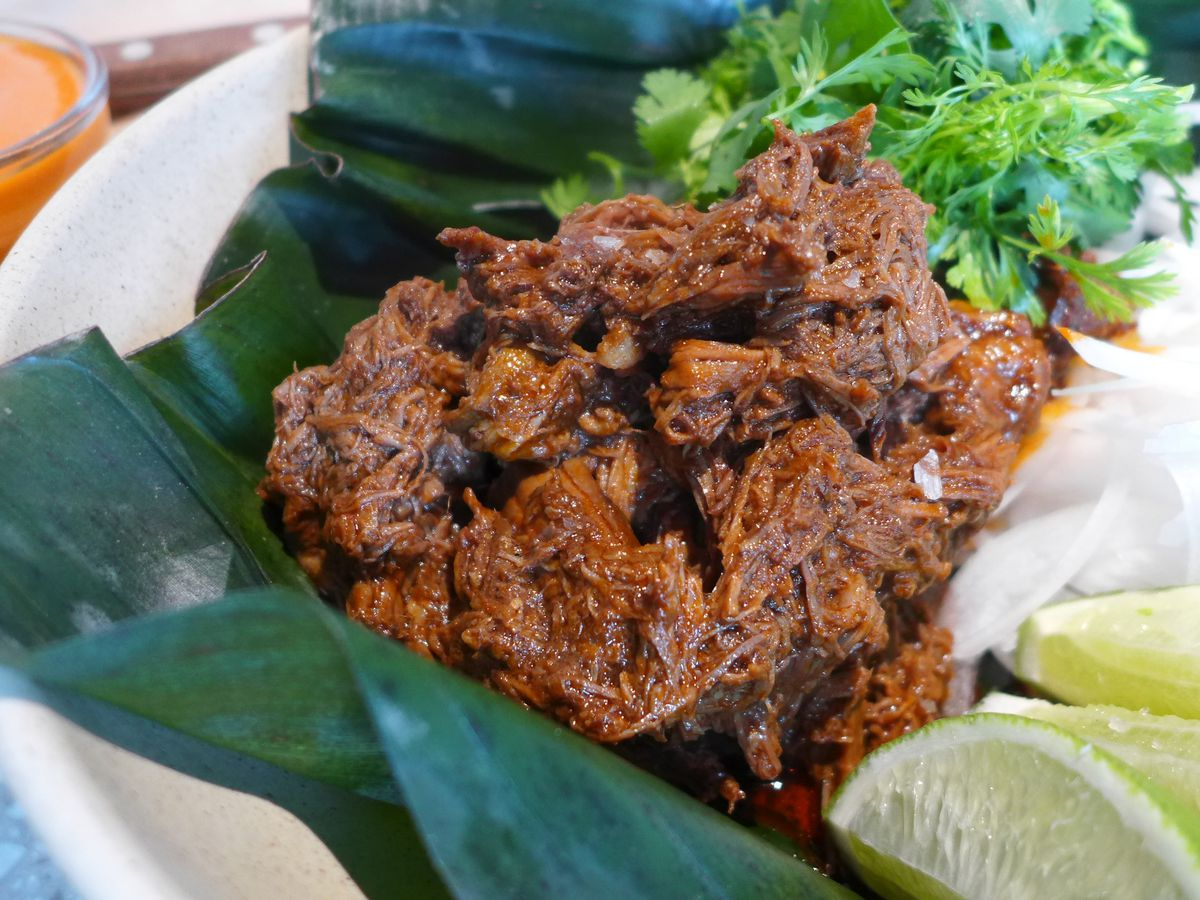 A banana leaf filled with chopped red meat.