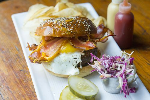The burger, topped with bacon and an egg, served with chips, pickles, and slaw.