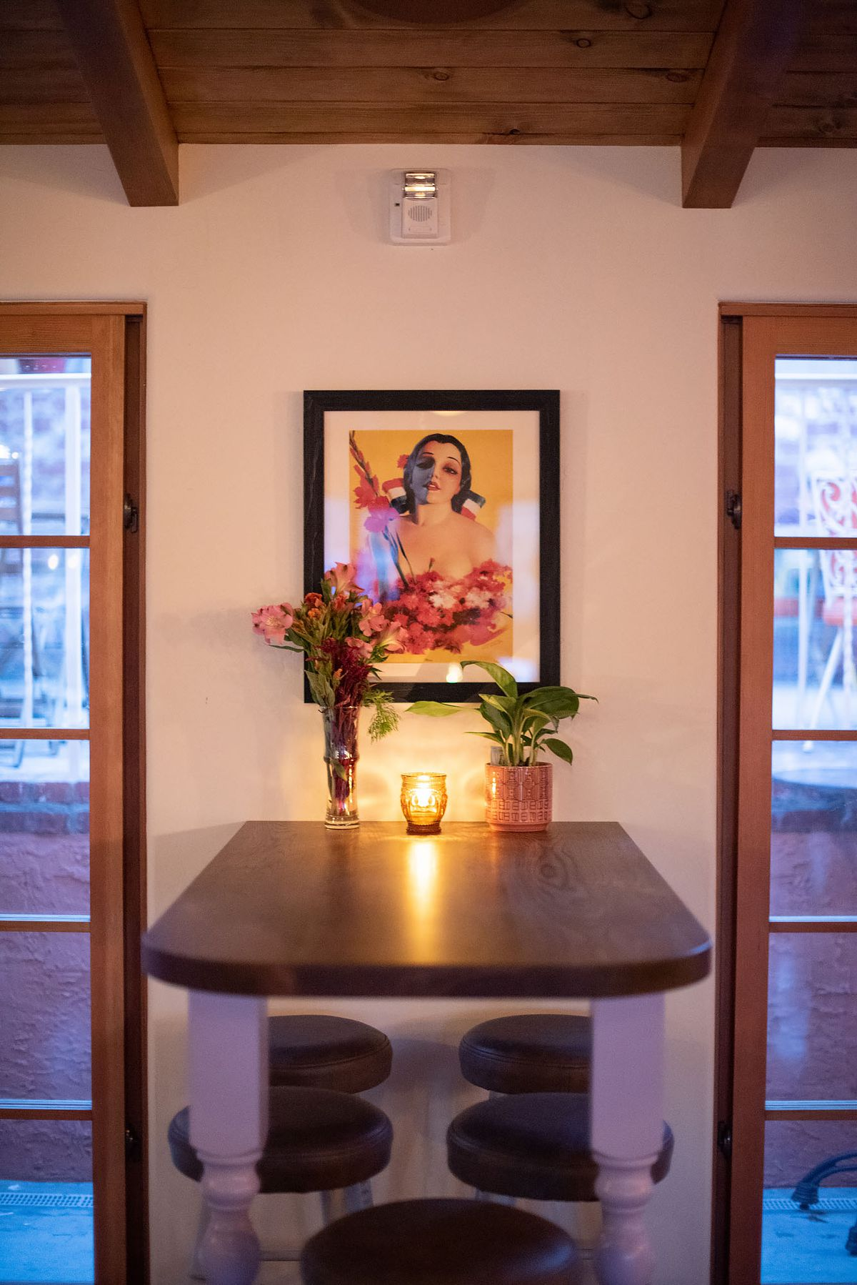 High table attached to wall with painting and candle.