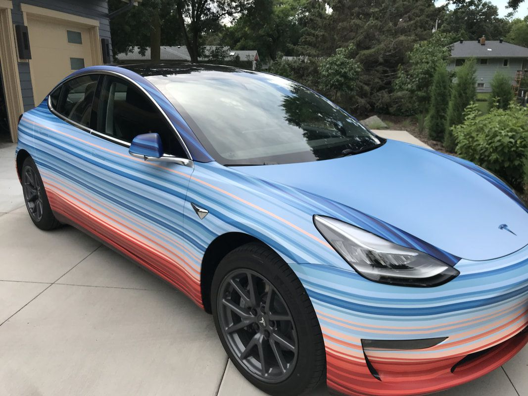 A Tesla Model 3 electric car with wrapped with the climate stripe pattern.