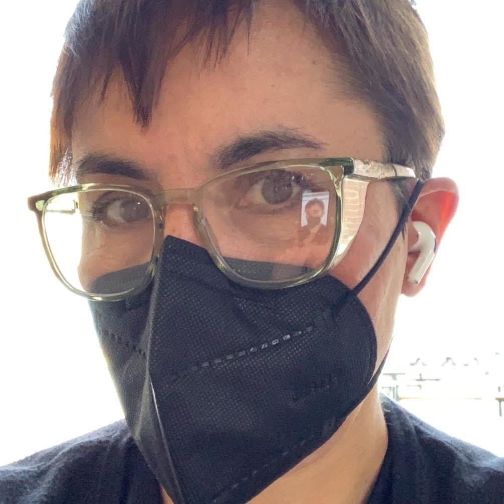 A self-portrait of a woman with short brown hair, glasses and a black KN-95 mask.