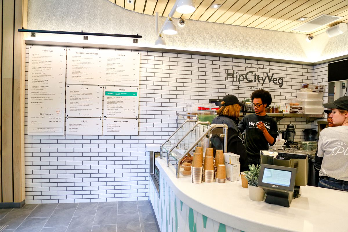 the hipcityveg storefront with workers behind a counter and a menu on the a white brick wall