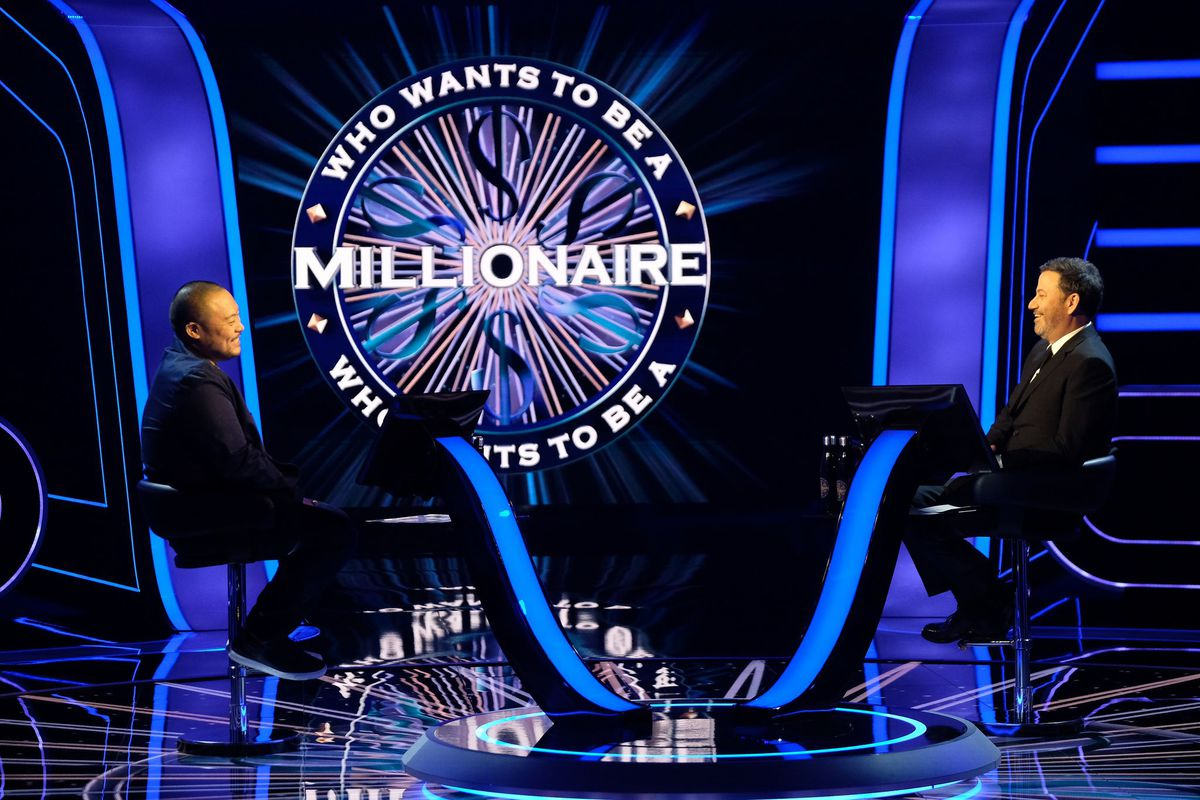 Chef David Chang and Jimmy Kimmel on the set of Who Wants to Be A Millionaire, with a large logo for the game show in the background