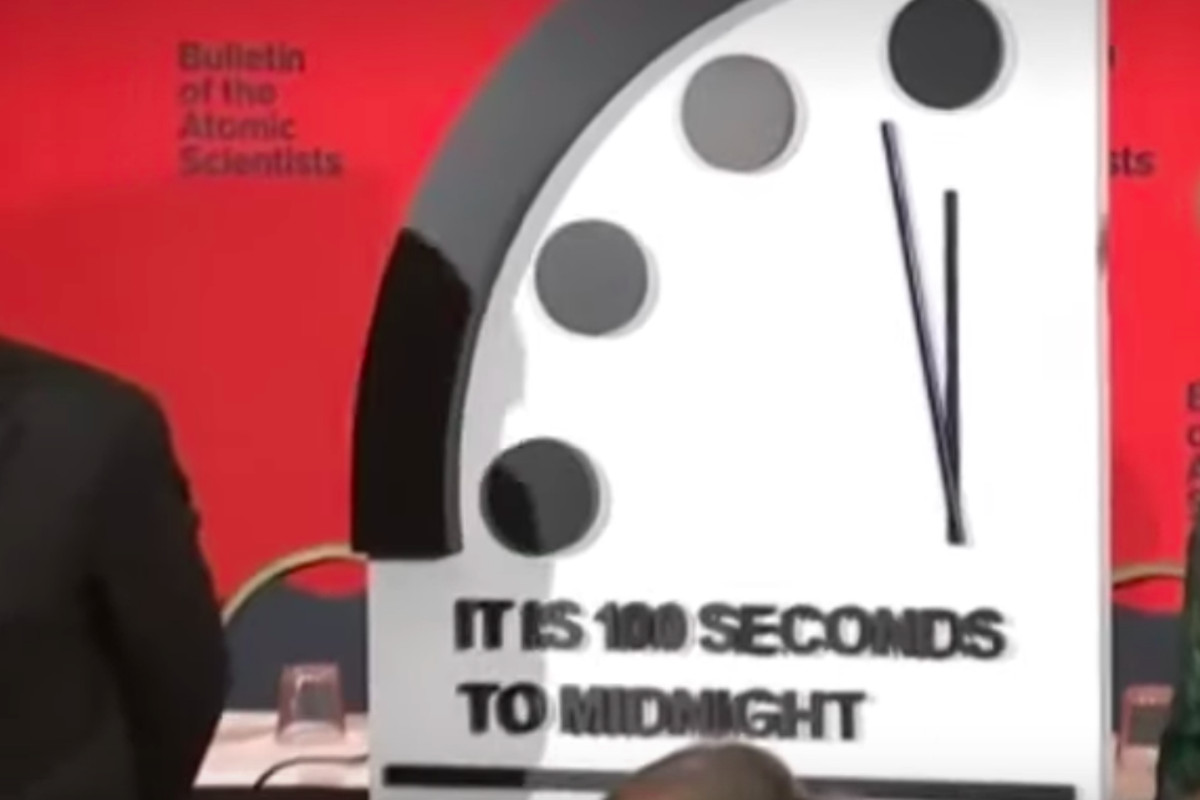 """A large clock face with hands pointing almost straight up reads, """"It is 100 seconds to midnight."""""""