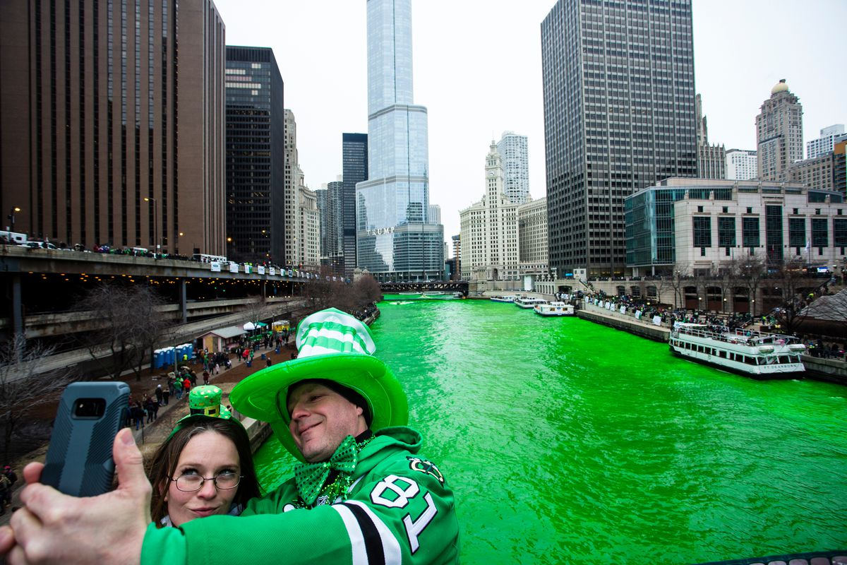 Stacey Peterson and Kevin McGuire take a selfie with the green Chicago River to celebrate St. Patrick's Day, Saturday, March 17, 2018.