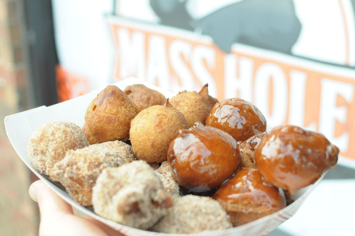 A paper tray brimming with three kinds of doughnut holes topped with cinnamon sugar, caramel sauce, and plain