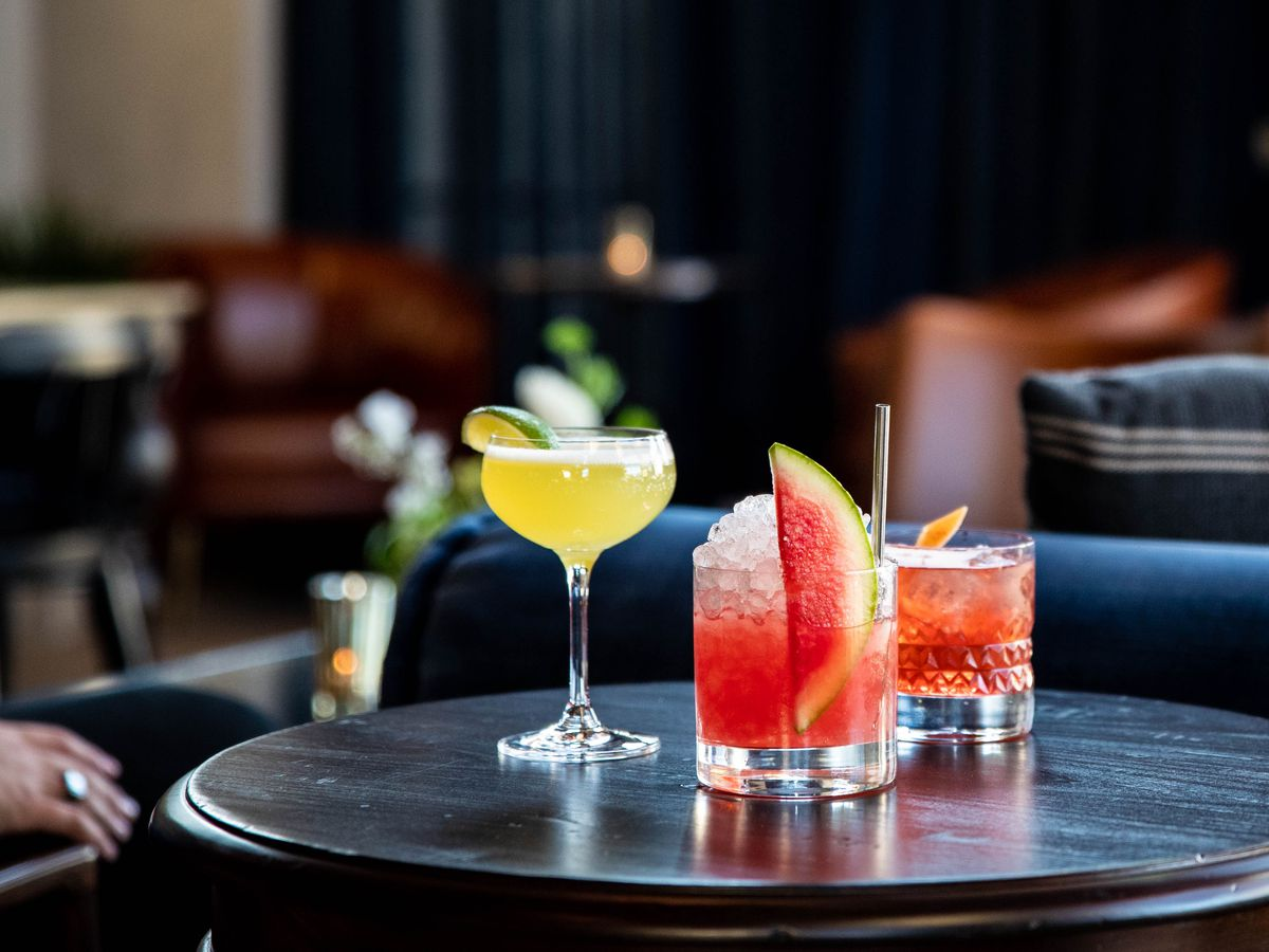 Three cocktails on a table in a hotel lobby