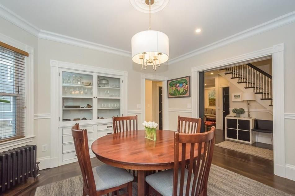 A formal dining room with built-in cabinets.