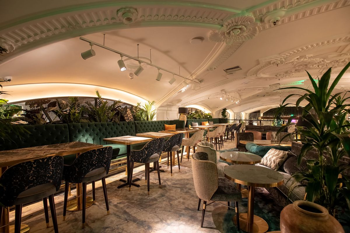 Modern seating inside a tall restaurant where the scalloped ceiling comes down the meet diners.