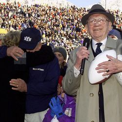 """Brigham Young football coach LaVell Edwards, left, hugs his wife, Patti, as Mormon church president Gorden B. Hinckley anounces that the BYU football stadium name will be changed to """"LaVell Edwards Stadium, home of the BYU Cougars,"""" Saturday, Nov. 18, 2000 in Provo, Utah. Edwards is retiring after 29 years of coaching at BYU."""