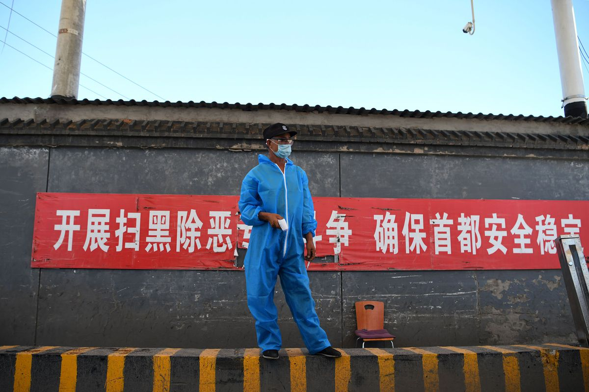 A man in a blue jump suit, a blue mask over his face, stands in front of a concrete wall with a sign in red and white.