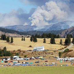 Smoke from the Table Mountain wildfire billows into the sky behind a fire camp set up at the Teanaway Grange Hall east of Cle Elum, Wash., Wednesday, Sept. 19, 2012.  The smoke produced by the wildfire, along with current weather conditions, have contributed to reduce air quality in the area to dangerous levels.