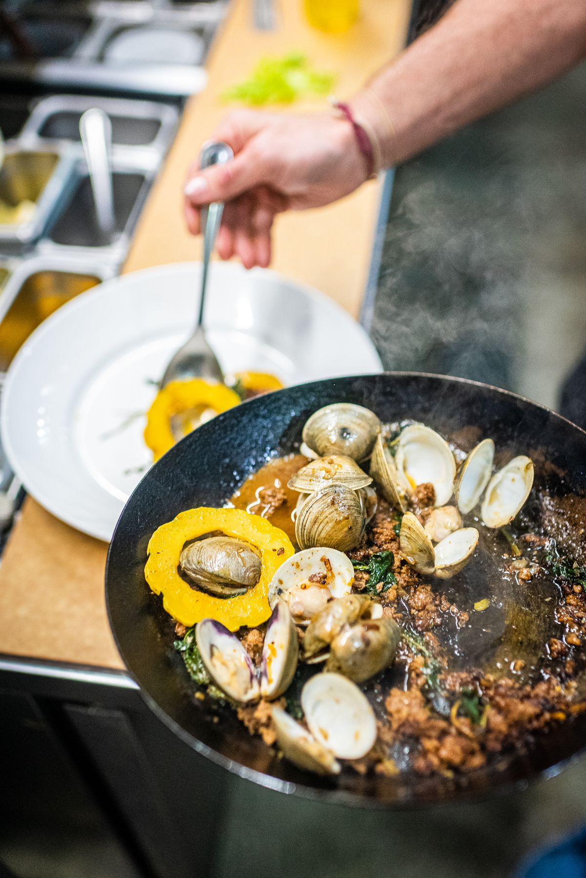 A pan of littleneck clams with squash and chorizo from Nina May