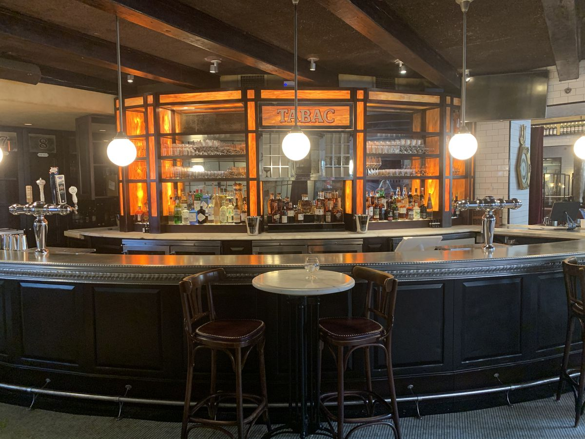 """A two-top marble table sits in front of a curved restaurant bar. Glowing orange panels, one featuring the word """"tabac,"""" illuminate the mirrored back of the bar."""