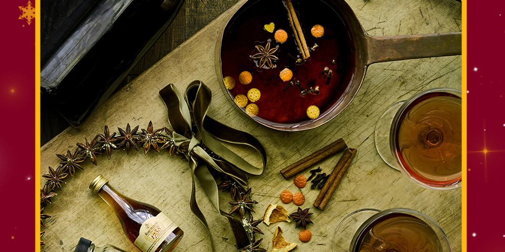A photo of mulling spices in a pot with two coups filled with red liquid and containers of mulling spices and wine. The scene is very festive.