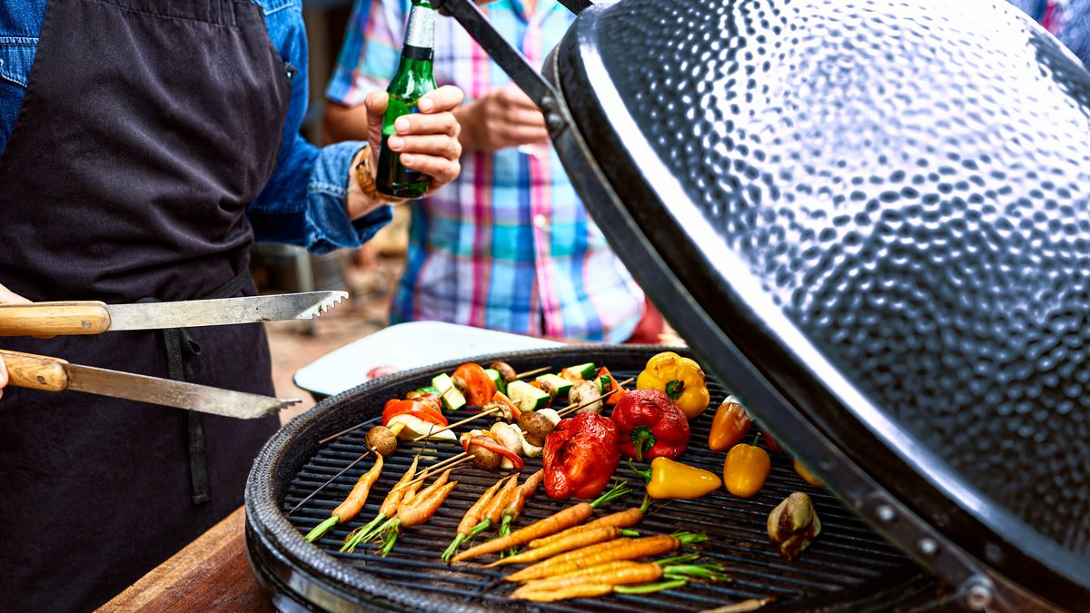 An array of vegetables is shown grilling on a kettle-style charcoal grill; two people stand next to it, one holding a pair of tongs.