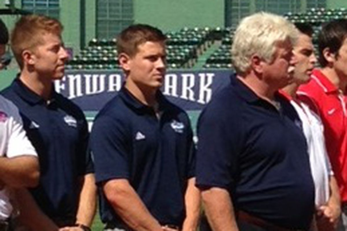 Forward Mark Anthoine, far left, stands with defenseman Brice O'Connor and head coach Red Gendron on the Fenway Park infield during September's announcement of the 2014 Frozen Fenway.