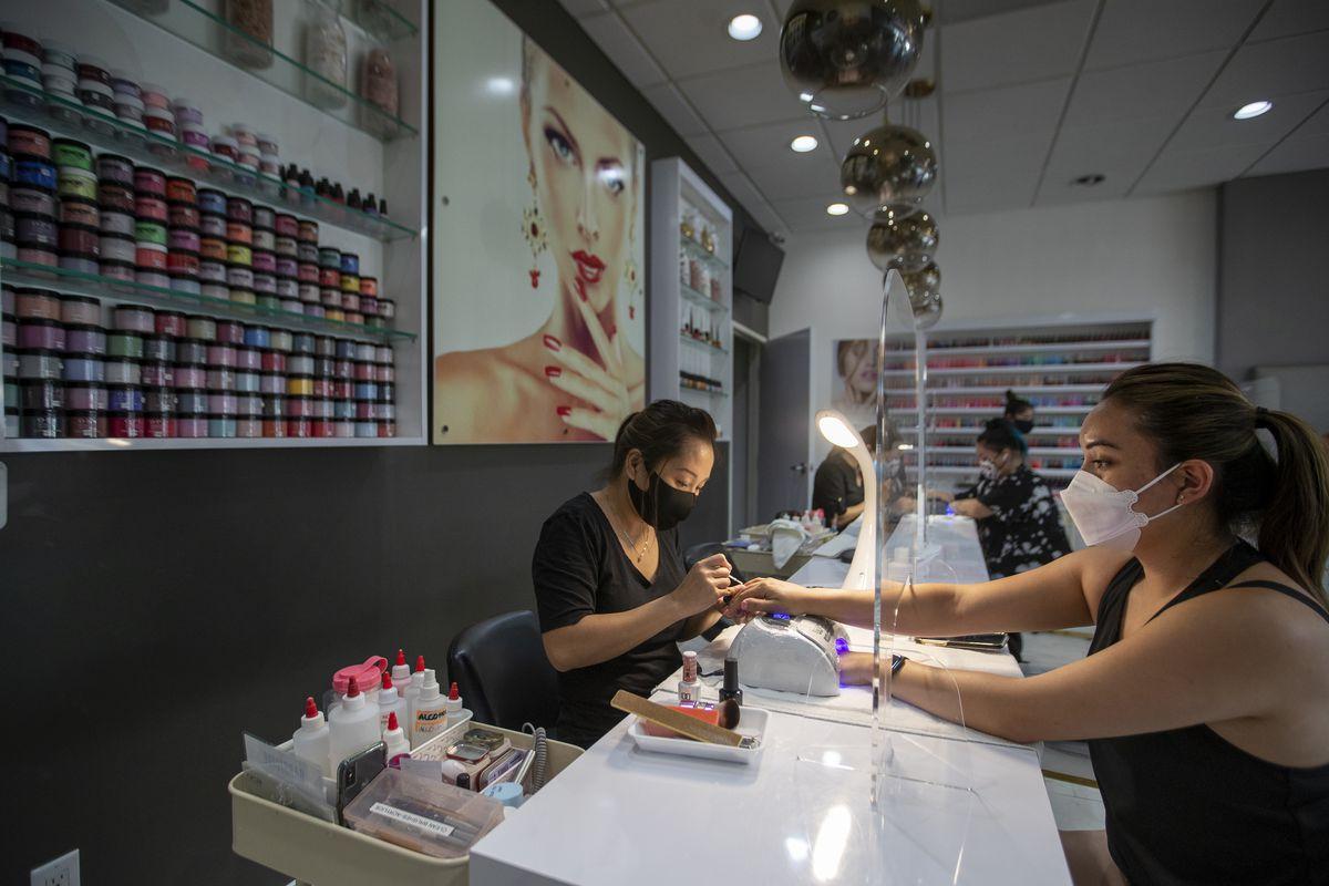 interior nail salon, technician giving woman manicure