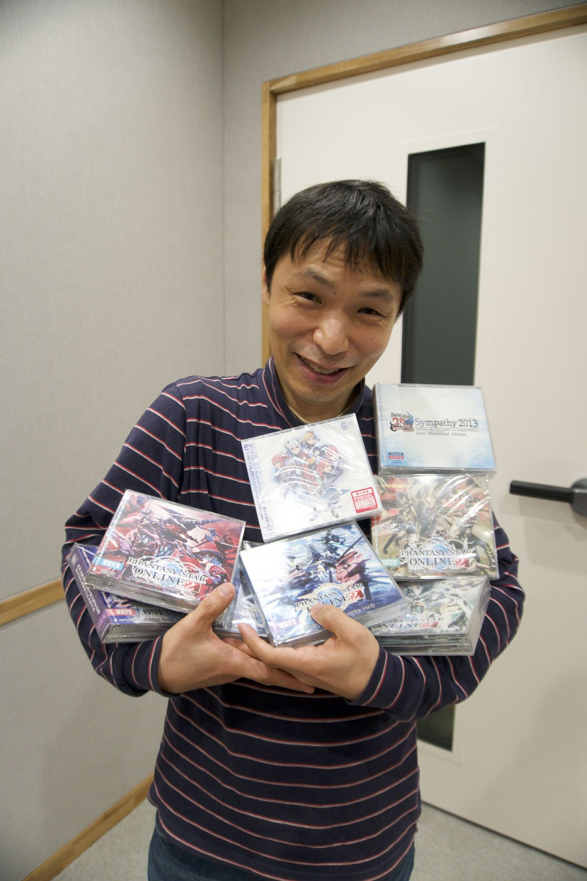 Hideaki Kobayashi carries a large pile of CD cases
