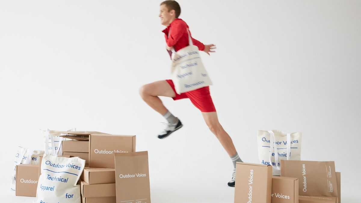 A man, carrying a tote, leaps across the screen.