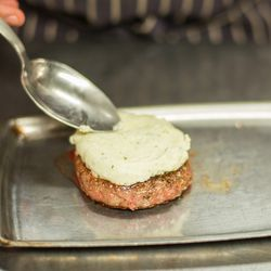 Béarnaise cheese is added to the cooked patty.