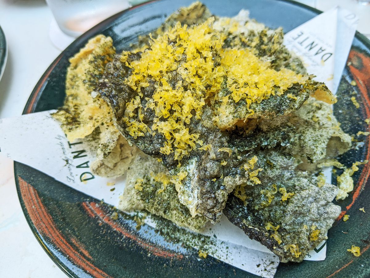 A heap of dark fried fish skins with a dry yellow condiment sprinkled on top.