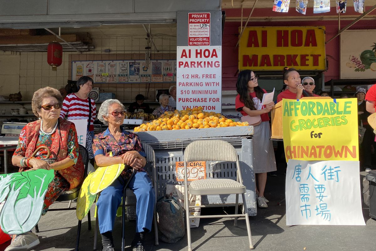 "A photo of people with signs sitting in the sun. The signs are drawings of vegetables. One sign says ""Affordable groceries for Chinatown."""