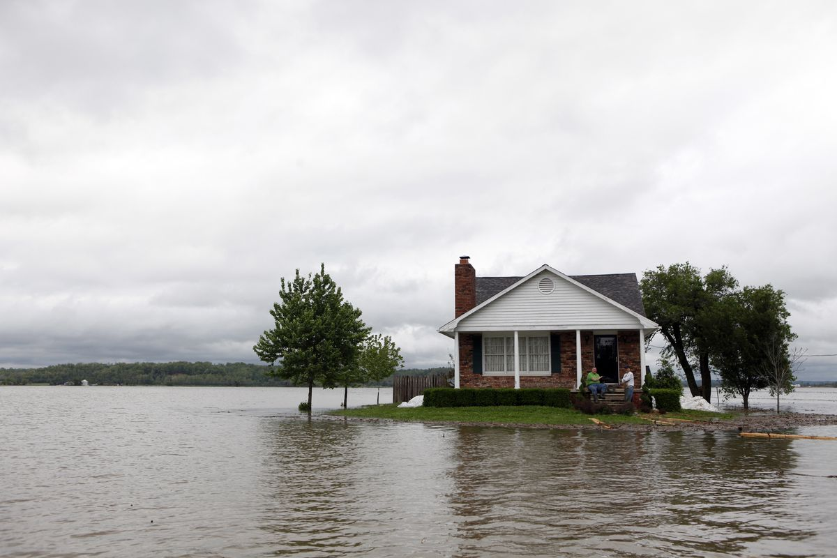 A traditional Colonial-style house fringed by green grass sits in what appears to be a large muddy lake, with two men resting on the front porch.