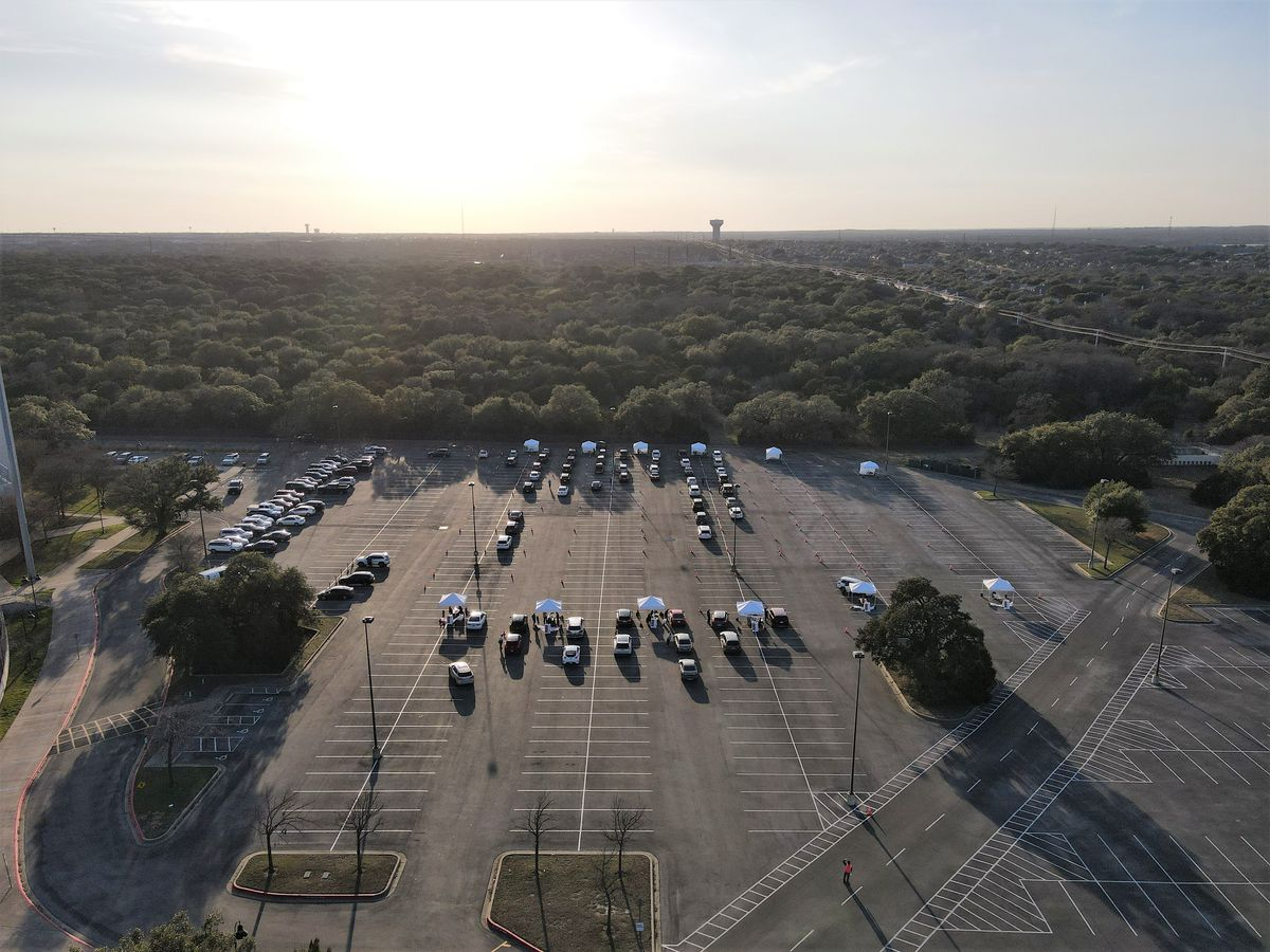 An overhead shot of a parking lot drive-thru vaccination site in Austin