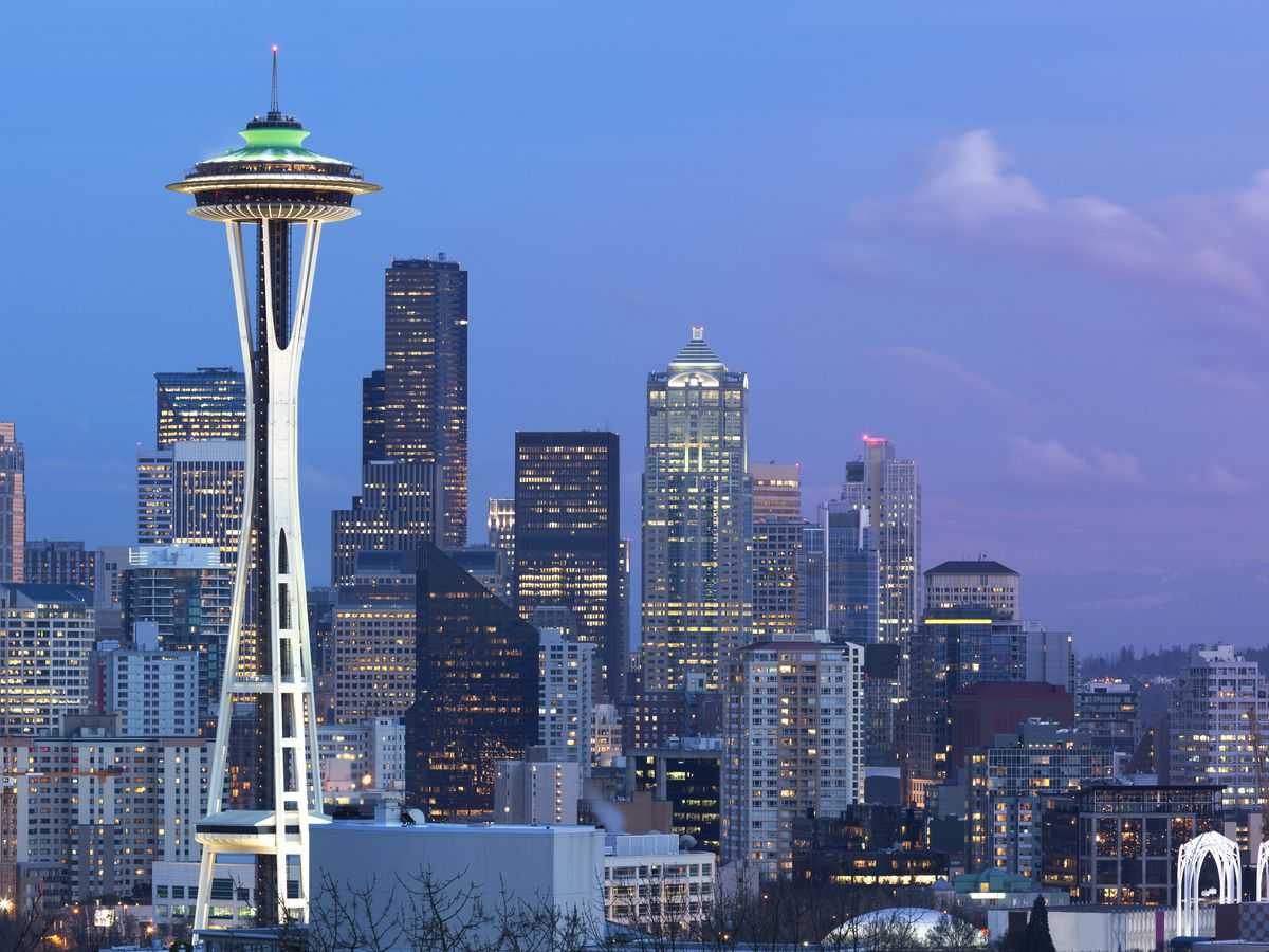 The exterior of the Space Needle in Seattle. The tower is tall with a green top. There is a city skyline in the background with buildings of varying heights.