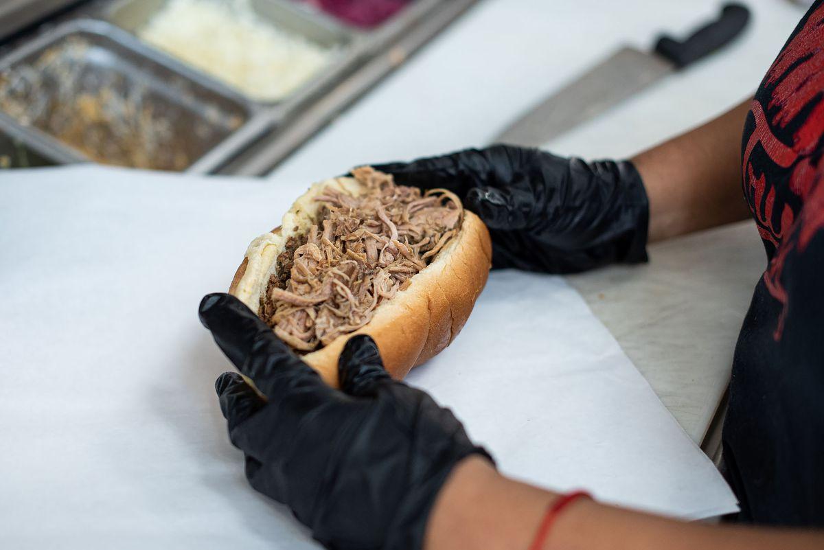 Dakis assemble le sandwich tripleta chez Triple Threat Truck avec des gants noirs.