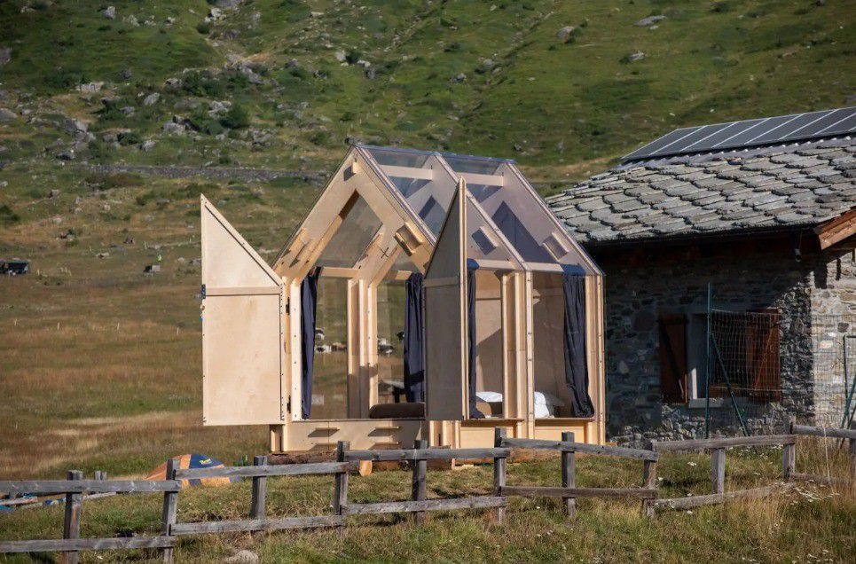 Pale timber cabin with glass roof sits next to old stone house.