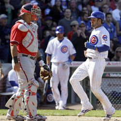 Chicago Cubs' David DeJesus, right, scores on Starlin Castro's one-run double during the eighth inning of a baseball game against the Washington Nationals in Chicago, Sunday, April 8, 2012. The Cubs won 4-3.
